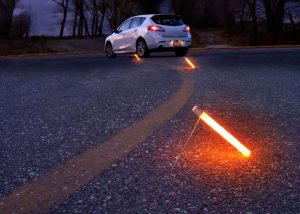 Bâton lumineux Flare Alternative posé au sol pour baliser un aire de stationnement de véhicule en panne